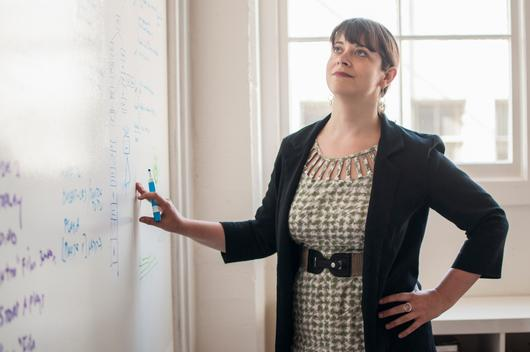 Woman in office handwriting on white board