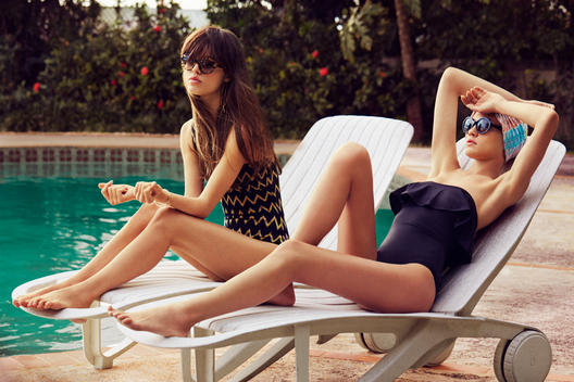 Two women lounging by the pool in bathing suit fashion.