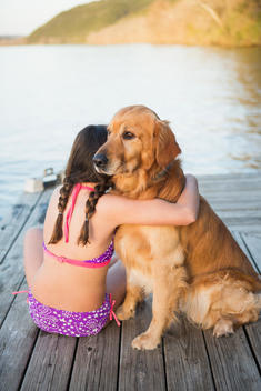 A young girl and a golden retriever dog sitting on a jetty.