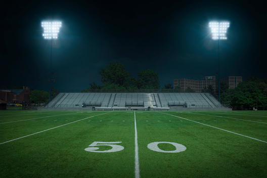 College football field with a view of the bleachers from the 50 yard line, at night, lits by the stadium lights.