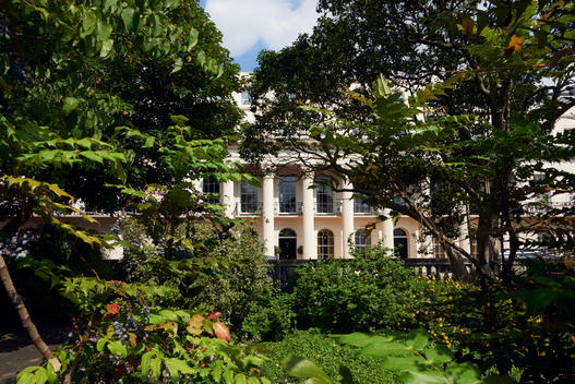 Classical white house with columns and garden in bright sunlight