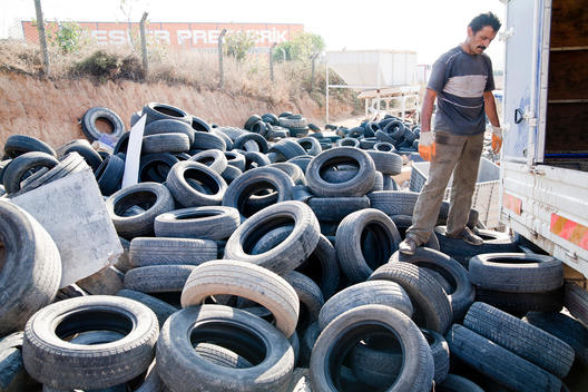 Labor man is looking around full of Tyres.