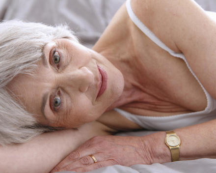 Senior Woman Relaxing On Bed, Smiling