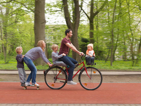 Family riding together on bicycle and skateboard