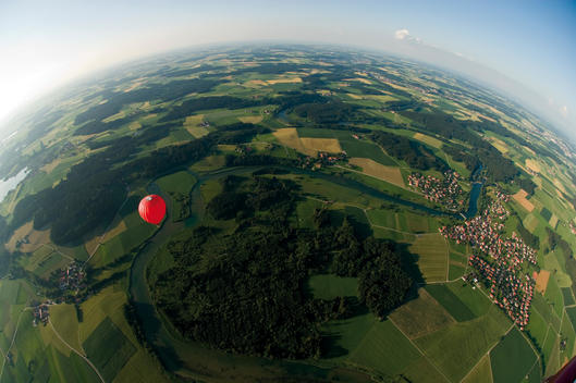 Germany, Bavaria, View of hot air balloon over pasture landscape