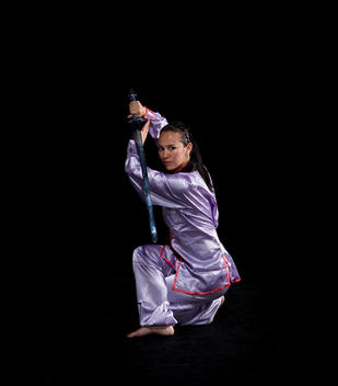 Pacific Islander woman practicing martial arts with sword