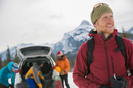 Smiling man with friends preparing for winter hike in mountains