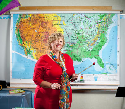 Smiling female teacher holds pointer in front of US map
