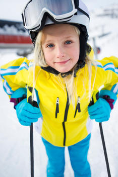 Young girl standing in her ski gear at a mountain ski resort.