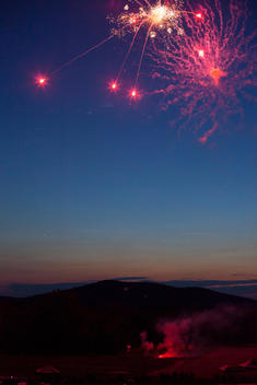 Fireworks being shot off over mountains in the country at sunset on the Fourth of July.