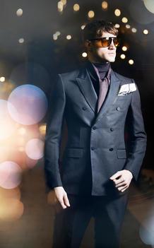 Male model in suit in cityscape lights
