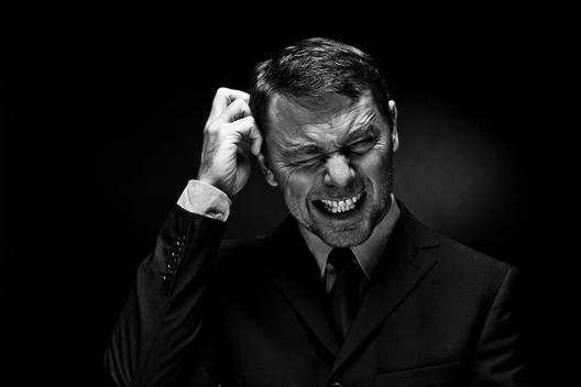 Mature man clenching teeth against black background
