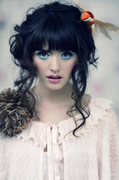 Portrait of a caucasian girl with dark hair up, pink lips, blue eye make up, wearing a pink cardigan with a bird in her hair, looking at the lens