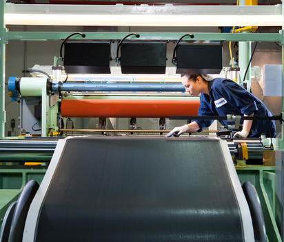 A female worker examines the material on a huge piece of machinery inside a factory
