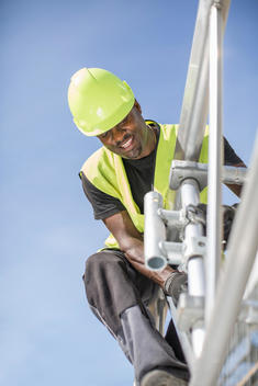 Low angle view of worker working on construction frame against clear sky