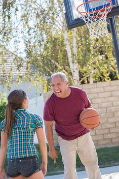 Grandfather and granddaughter playing basketball in driveway