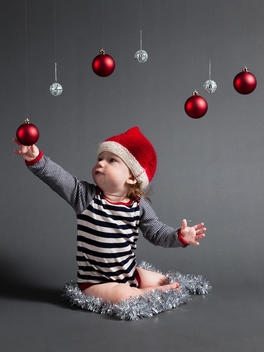 Nine month old baby boy playing with baubles and wearing a Christmas hat.