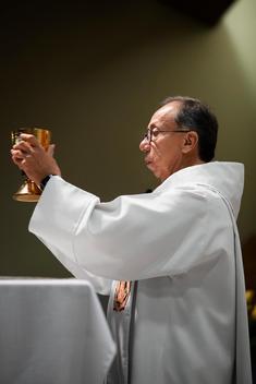 Hispanic priest giving sermon in Catholic church