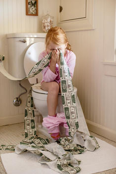 girl on toilet blowing nose with money toilet paper
