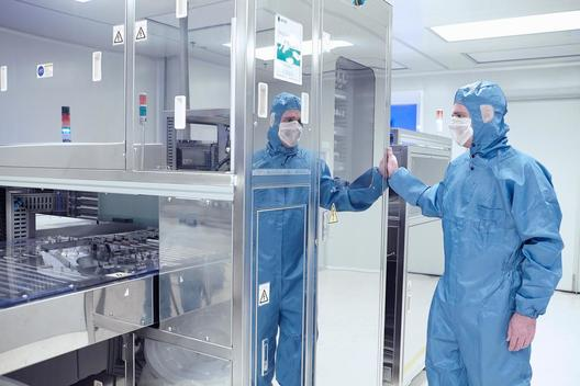 Male worker inspecting machinery in flexible electronics factory clean room