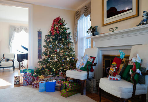 A formal living room with Christmas tree and gifts