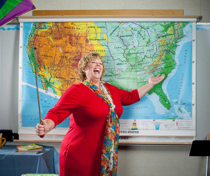 A happy female teacher is pointing to large US map