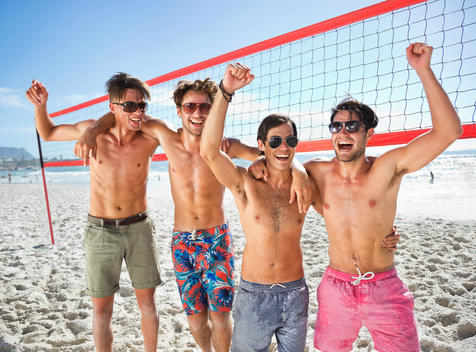 Portrait of enthusiastic friends on beach volleyball court