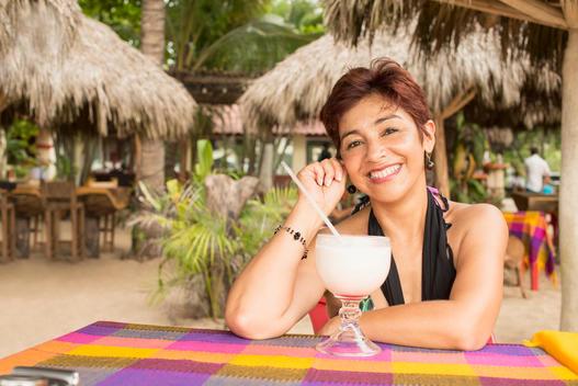 Hispanic woman enjoying tropical drink at resort