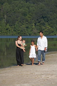 Multicultural Family Walking On Beach