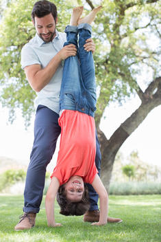 Father holding son upside-down in backyard