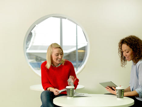 Two young businesswomen in chill out area office discussing business