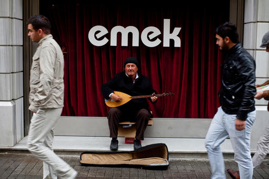The street musician in Istanbul plays old Turkic instrument in the street of Istiklal (Liberation) and singing Turkish folk music and behind him on the shop it s written \'Labor\'.