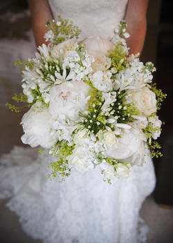 A woman in a white dress, a bride holding a bridal bouquet of white flowers, large white roses and peonies, with delicate yellow flowers and green leaves.