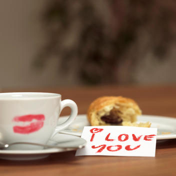 Cup of coffee with lipstick kiss, croissant and I love you-sign