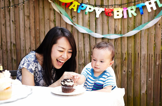 Mother and baby boy smiling with birthday cake