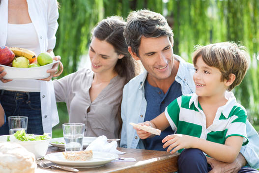 Family eating together outdoors, father holding son on lap