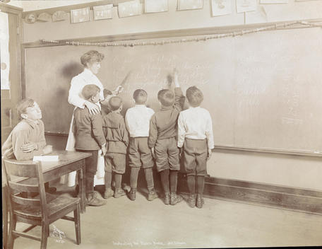 A Female Teacher Working With A Group Of Boys At In A Class For Developmentally Disabled Children.
