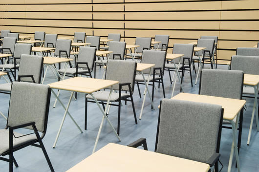 The main hall of a modern secondary school set out for exams with rows of desks and chairs