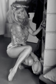 Caucasian blonde woman with big 60\'s hairdo, bow in her hair, crouching down one leg out, wearing a lace top, holding a hat surrounded by a walkin wardrobe