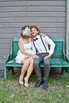 Portrait of bride and groom sitting on bench, bride kissing groom on cheek