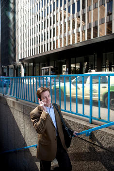 A Business Man Walks Upstairs Onto A Busy Chicago Street While Talking On A Cell Phone.