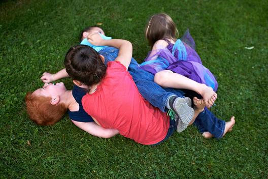 group ok kids wrestling on the grass