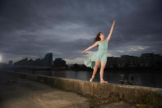 Ballet dancer reaching upwards on wall