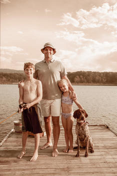 Caucasian father, children and dog smiling together