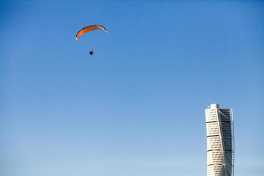 Low angle view of parasail in mid-air and Turning Torso skyscraper against clear blue sky