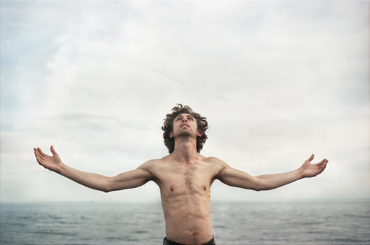 Portrait Of A Man Depicting Christ In Front Of The Water With His Arms Outstretched.