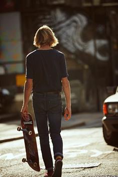 Man walking away with skateboard on street