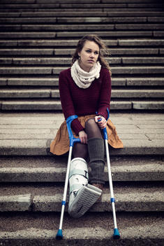Germany, Kiel, Woman with cast and crutches sitting on stairs