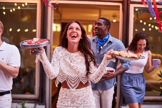 Woman laughing serving hor d\'oeuvres at Fourth of July party