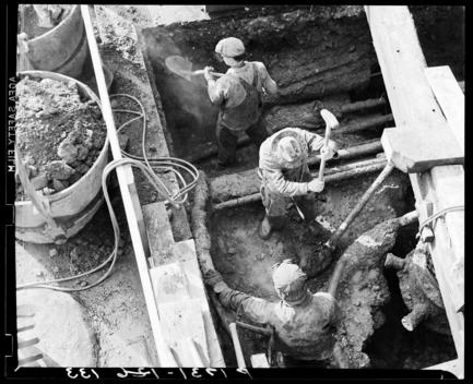 Three Men In A Pit, One Has A Sledge Hammer, Another Has A Shovel, The Third Looks On.